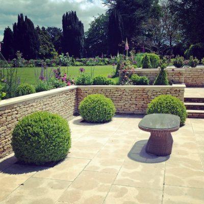 Box ball topiary in country garden terrace by Bath Garden Design